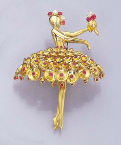 AN 18K GOLD AND RUBY BALLERINA CLIP BROOCH, BY VAN CLEEF & ARPELS The ballerina wearing a gold sequence dress with collet ruby detail, to the ruby and diamond head dress and small bouquet of flowers, circa 1945, with French assay marks Signed Van Cleef & Arpels, N.Y., 11903