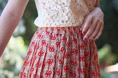 Cute combination of the white crochet blouse and the red floral skirt.