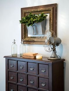 One of Joanna's custom creations for this space was repurposing a galvanized metal dustpan as a wall vase and hanging it within an antique frame. Other vintage touches in the foyer include a sturdy wood chest mimicking the appearance of antique file cabinets, an antique fan and antique seltzer bottles.