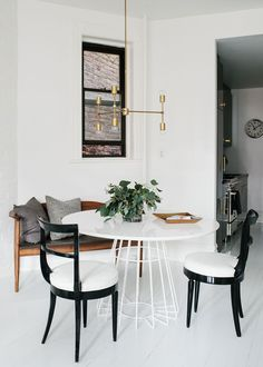 Gorgeous, Scandinavian dining room space with white shiplap floors, a wooden bench decorted with velvet throw pillows, a gold geometric pendant light, white dining table and black and white chairs | BHDM Design