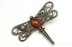 This beautiful vintage dragonfly pin in sterling silver features delicate filigree-like wings and a large Baltic amber body. It is beautiful with