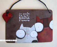 """Targa """"In questa casa regna l'amore"""" realizzata su supporto di laminato. Illustrato in pezzo unico sul davanti e finito a tinta unita sul retro. Cuore decorativo in ceramica smaltata. Dimensione..."""