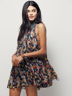Floral Pleated Mini Dress   In a shapeless silhouette, this floral printed chiffon mini dress features pleat detailing.  High rounded neck and dropped armholes.  Lined.
