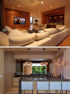 This modern house has a casual living room with a large comfortable couch. Beside the living room is a bar, with a mirrored wall and sculptural wood pendant lights.