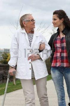 handicaps: Mujer joven ayudando a los ancianos a caminar con una muleta