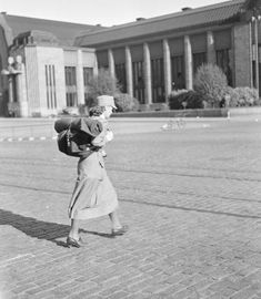 Sunny summer day in Helsinki. Member of Lotta Svärd voluntary auxiliary organization heading to the railway station for her assignment in the east. 25 June 1941. (first day of hostilities)