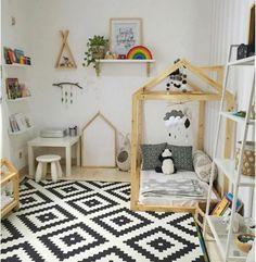 tapis en blanc et noir, motifs géométriques, lit maisonnette en bois, matelas blanc, coussins en noir et blanc, table et tabouret blanc, etagere murale livres, mobile bébé, chambre montessori