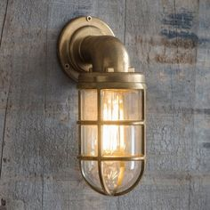 A raw cast brass outdoor wall light, with thick piping style arm and cage that surrounds the glass shade. Click the image to buy now Coastal Lighting, Outdoor Wall Lighting, Exterior Lighting, Bathroom Lighting, Fish Lamp, Brass Lantern, Wall Lights, Ceiling Lights, Hanging Lanterns