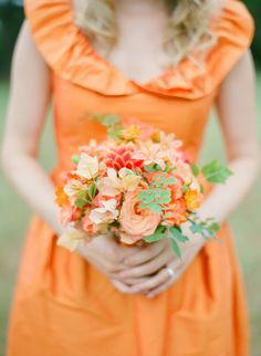 Orange bridesmaid's dress and peach and orange bouquet