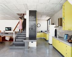 Concrete floors, countertops, stair, and yellow cabinetry.