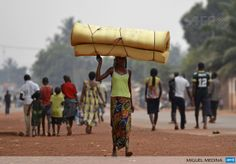 CENTRAL AFRICAN REPUBLIC, Bangui : A woman carrying a mattress on her head flees the Gobongo district in Bangui on December 26, 2013. AFP PHOTO/ MIGUEL MEDINA