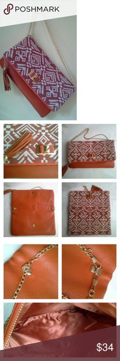 """Aztec Foldover Clutch Southwestern style aztec fabric, and a tasseled zipper pull. Vegan pebbled leather on one side, fabric on the other. Strong magnet keeps it tightly folded in place. Rust orange & ivory w gold tone hardware. Chain strap can be doubled to a shorter length, let out to use as a crossbody, or detatched altogether. Approx dims: 12"""" wide x 13.5"""" tall when open, 7.5"""" tall folded, chain strap 44"""". Some mfg glue on the goldtone bow embellishment. Never used, and clean inside/out…"""