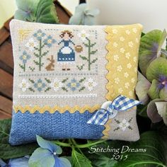 Stitching Dreams - For this finish, I used some complementary blue and golden-yellow fabrics and ric rac and added a small accent square featuring one of the stitched white flowers in the lower right. At the corner where the ric rac intersects, I placed a white button topped with a cut of blue and white gingham ribbon. I'm so pleased with how it turned out!
