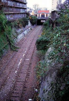 Below-grade railroad track, with small building above it in background Small Buildings, I Want To Travel, Train Tracks, Travel Abroad, France Travel, Abandoned Places, Wonderful Places, Paris France, Railroad Tracks