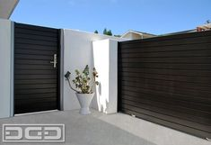 Patio and courtyard gates in solid wood with a modern horizontal slat design. Gorgeous espresso-stained wood grain & modern knob