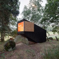 Dezeen | Tag: Blackened wood | Forest Retreat by Uhlik Architekti rests on a boulder in a Bohemian wood