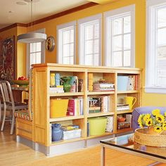 A partial wall and bookcase unit bridges the kitchen and sitting room and holds cookbooks, magazines, and essential toys for kids (in color-coded bins, of course).