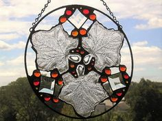Stained Glass Art Panel|Round Leaf Panel|Autumn Colors|Autumn Leaves|OOAK|Glass Art|Handcrafted|Made in USA  I love finding objects that I can upcycle into my glasswork, making for unique one of a kind (OOAK) items. This round panel is one such piece. Made with three little glass dishes in the shape of leaves, it is also embellished with beveled glass and several glass gems in autumn colors. It measures 12 in diameter, is finished in traditional black patina, and has a chain attached for…