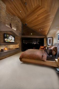 This master bedroom features a natural wood ceiling, a stone fireplace, and access to a private patio. Source: http://www.zillow.com/digs/Home-Stratosphere-boards/Luxury-Bedrooms/