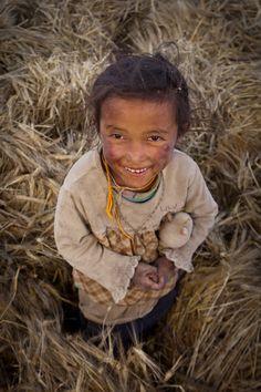 Little girl standing in the wheat fields of western Tibet