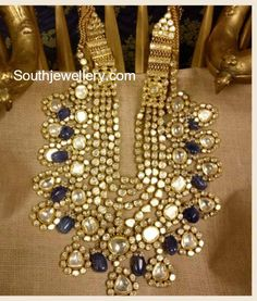 22 carat gold encrypted mind blowing bridal jadau necklace from Ksrala. Syndicate Polki and Tanzanite stones combination grand kundan jadau set enhanced with blue sapphire beads Wedding Necklace Set, Wedding Jewelry Sets, Bridal Necklace, Bridal Jewelry, Bridal Kundan Jewellery, Gold Necklace, Jewelry For Her, Dainty Jewelry, Fine Jewelry