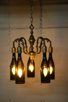 20 bright ideas diy wine beer bottle chandeliers beer bottle rewired this antique chandelier and altered the design by turning the arms upside down i then drilled and threaded brass cups to accept the wine bottle aloadofball Image collections