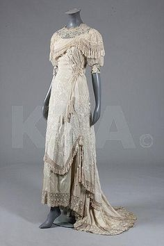 A bridal gown of Cantonese embroidered silk, circa 1910, with chiffon puff sleeves, lavishly embroidered swathed silk over-dress trimmed with fringes and tassels, Kerry Taylor Auctions