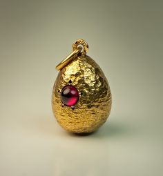 A Russian Antique Ruby and Textured Gold Egg Pendant, 1908-1917. The 14K gold miniature egg is designed to resemble a gold nugget, embellished with a cabochon cut ruby.