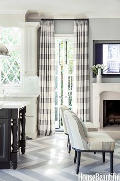 Grey and white kitchen by Mary McDonald with striped drapery and chevron pattern floor