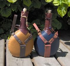 Handstiched leather covers small round bottles. The cork is attached with a leather lace, and beads decorate the bottle. A useful and pretty accessory. I make them for sale at medieval events.