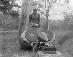 """Robert Sutherland Rattray Date of Photo: 1921 - 1932 circa Continent: Africa Geographical Area: West Africa Country: Ghana Cultural Group: Akan Asante Format: Glass negative Size: 101 x 125 mm Acquisition: Herbert Crook - Donated March 1941 Description Ntumpane [pair of drums] with gramophone in foreground, on which Rattray recorded a """"set piece"""" ... a sacred drum-history of an important Ashanti division [captioned: """"Ntumpane (talking drums)""""]."""
