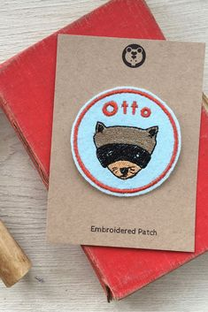 This unique custom name patch with a cute raccoon design would be perfect for decorating clothing, camp blankets or school pencil cases and bags. Custom Name Patches, Embroidered Name Patches, School Pencil Case, Camping Activities For Kids, Yosemite Camping, Cute Raccoon, Stationary School, Camping Blanket, Customized Gifts