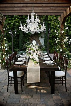 Outdoor table setting. Juxtaposed chandelier against rustic wood. Simple white table runner.