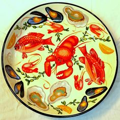 Large ceramic pasta bowl in the seafood pattern depicting a lobster, red snappers, oysters, mussels, shrimp, lemons, and kelp  painted by Geoff Graham of Cinnabar Ceramics in Vallejo, California, limited edition 2015