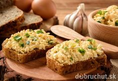 Whole wheat sandwiches with egg and cheese spread on wooden stump.