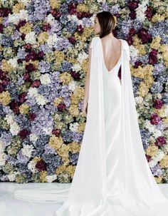 Vestido de novia sin mangas en crepe de seda con pliegues a la cintura creando efecto reloj de arena. De sus hombros surgen lazadas japonesas que caen en la espalda en forma de capa.
