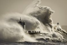 People watch and photograph enormous waves as they break on Porthcawl harbour, South Wales.Ben Birchall