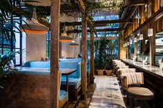 Toward the back of the main dining room, a more intimate area features vibrant blue-leather booths with wicker detailing situated under a plant-covered pergola. Bar seats along a steel-clad counter offer views into the open kitchen.