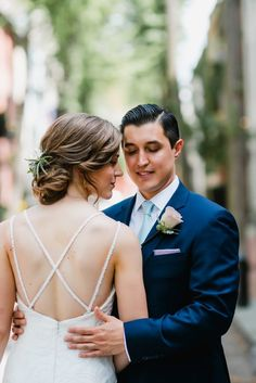 Bride in strappy low back wedding dress and loose romantic hair. Groom in navy suit and pink rose boutonniere. Photo by Love Me Do Photography in Philadelphia. Full wedding shared on Flutter Social.