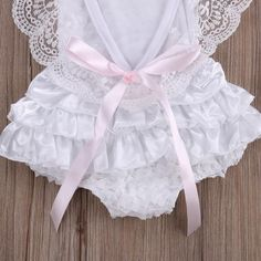 White lace Romper    A mama fav!  Soft lace on shoulder  Elegant for baptism or first birthday  Great baby shower gift  Pink tie in the back  Cotton / polyester            Size  Length  Bust*2  Age      3  35 cm  24 cm  0-3 Months      6  37 cm  26 cm  3-6 Months      9  39 cm  28 cm  6-9 Months      12  41 cm  30 cm  9-12 Months      18  43 cm  32 cm  12-18 Months