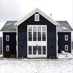 Black house juxtaposed with white window trim.
