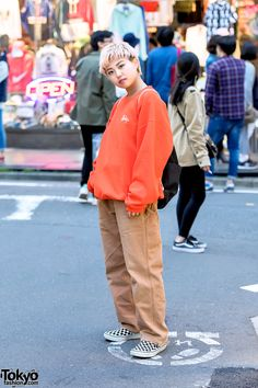 20-year-old Terumi - who works at Stussy Harajuku - wearing a Stussy sweatshirt with Carhartt pants, a Carhartt backpack, and classic Vans checkerboard slip-ons. Full Look