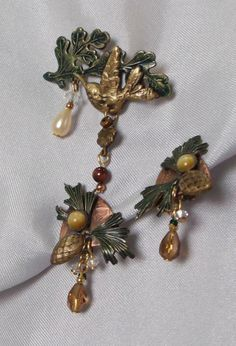 Offered are early pieces of naturalistic and beautifully detailed pieces from the Silver Forest jewelry company in Vermont! This pieces compliment each other wonderfully! Earrings have little pine-cones in antiqued gold and enameled green accented with set sun-stone and accented with a faceted piece of amber topaz dangling beneath. These are clip on style and measure 1.25 total length. Pin is a gorgeously detailed hummingbird with enameled green leaves, a teardrop pearl and tiger eye…