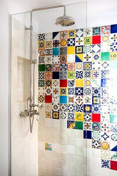 This mix-and-match tiled wall brings an exotic touch to an otherwise plain showering space – a frameless pane of glass prevents the water spraying outside the designated area without detracting from the colourful design element.  --  Costas Picadas/GAP Interiors