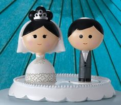 """These darling bride and groom figurines are a delightful addition to any wedding cake top! Inspired by traditional Japanese kokeshi (hand-painted wooden dolls), they feature different ethnicities of brides and grooms that can be mixed and matched to best represent you as a couple. Let them stand on their own, or fit them in the scalloped-edge base (sold separately). Cake Top Figurines measures 4.5"""" tall.Base measures 6.25"""" in diameter and .75"""" tall.Added August 28, 2011 et"""