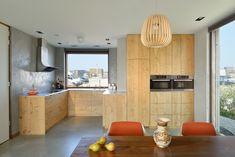 Cucina piccola moderna con pareti di cemento e mobili in legno. Molto luminosa e originale