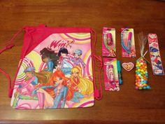 Winx Club birthday party goody bag with drawstring backpack, bookmark, lip gloss, lip balm, nail polish, hair mascara, ring, and candy.
