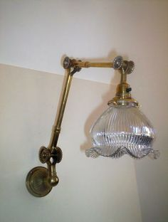 """A  brass triple-adjustable wall light with stamped mark """"Dugdill Patent"""" complemented with a holophane glass lampshade. England c1920-30"""