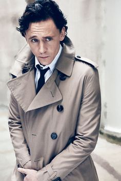 Tom Hiddleston with black hair wearing a trench coat and raising one eyebrow.