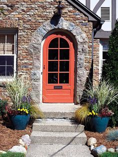 Feng Shui door. Consider the style of your home and choose colors accordingly. This orange-red door works well against the stone facade. Clear path, balanced landscaping... all add up to good Feng Shui enhancement!